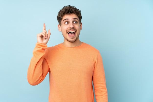Uomo caucasico sulla parete blu che intende realizzare la soluzione sollevando un dito