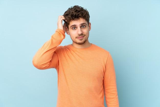 Uomo caucasico sulla parete blu con un'espressione di frustrazione e non comprensione