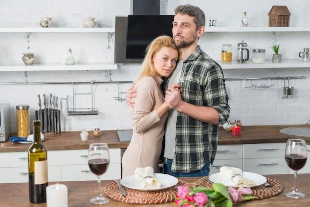 Uomo che abbraccia con donna vicino a tavola con fiori, bottiglia e bicchieri di vino