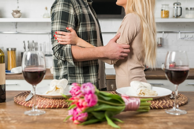 Uomo che abbraccia con donna vicino a tavola con fiori e bicchieri di vino