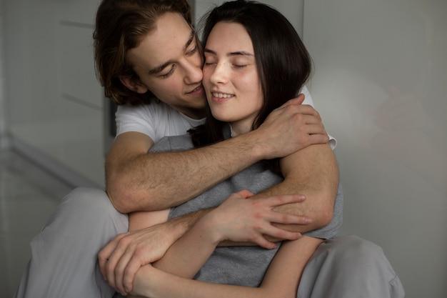 Uomo che abbraccia la fidanzata mentre sorridente