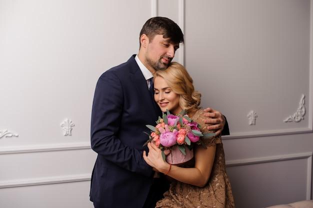 Uomo che abbraccia la sua donna in abito beige con il mazzo di fiori e guardando verso il basso
