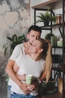 Uomo che abbraccia la sua ragazza tenendo la tazza di caffè