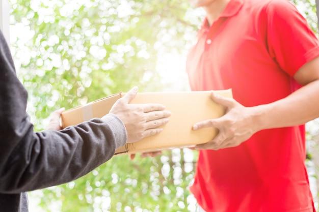 Uomo che accetta una consegna di scatole dal corriere del servizio di consegna. isolato su uno sfondo bianco.
