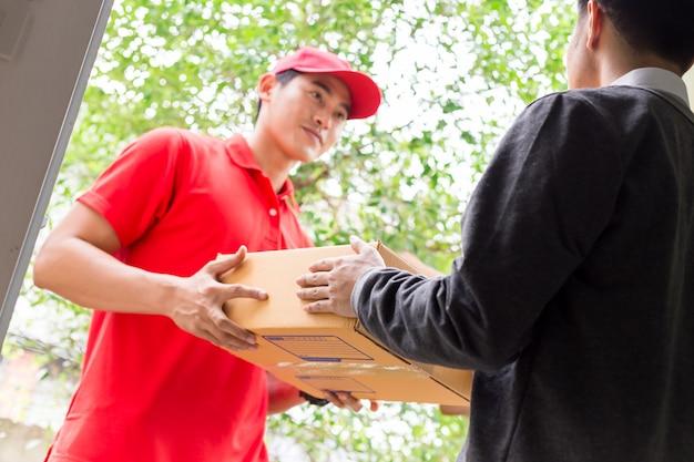 Uomo che accetta una consegna di scatole dal corriere del servizio di consegna.