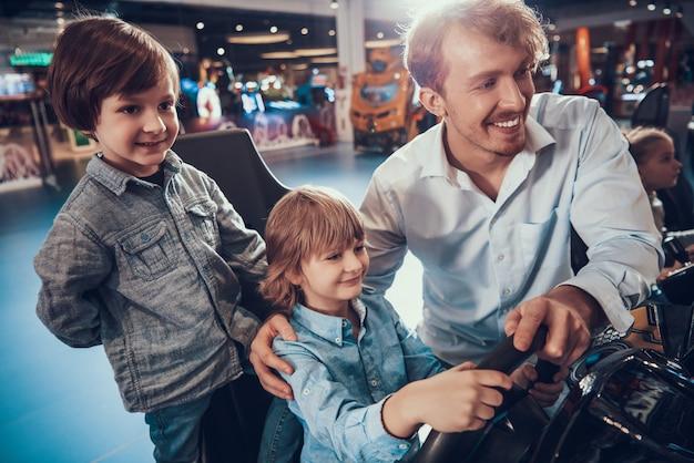 Uomo che aiuta cute boy giocare a racing simulator game