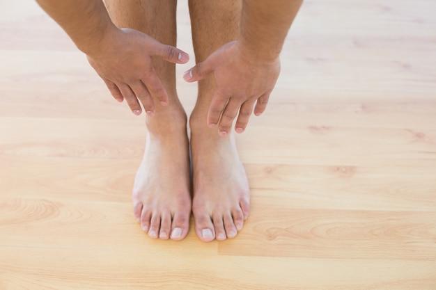 Uomo che allunga le mani verso i suoi piedi sul pavimento in parquet