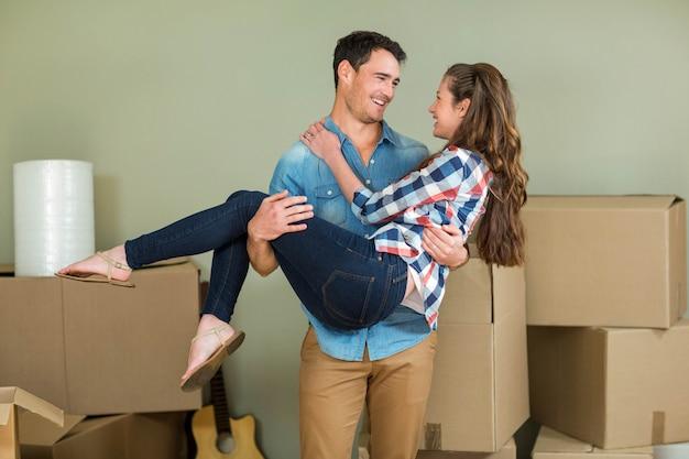 Uomo che alza la donna tra le sue braccia nella loro nuova casa
