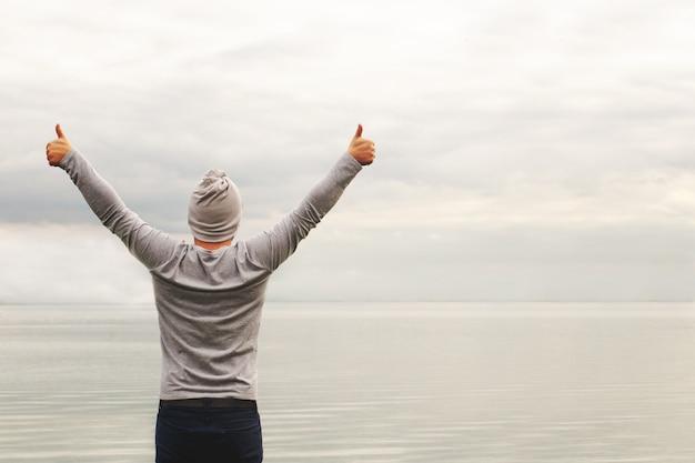 Uomo che alza le sue braccia da un lago