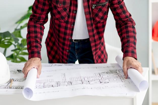 Uomo che apre il progetto architettonico