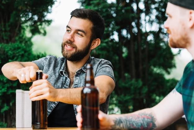 Uomo che apre la bottiglia di alcol con il suo amico