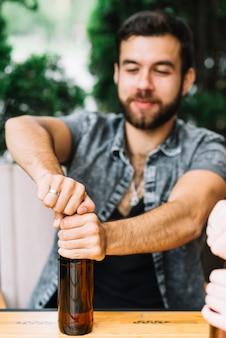 Uomo che apre la bottiglia di alcol sul tavolo