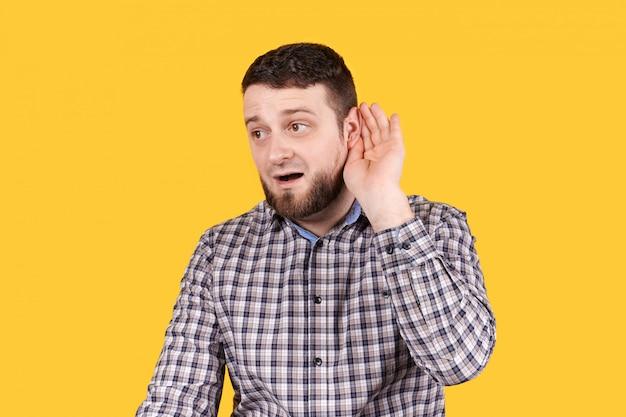 Uomo che ascolta con la mano sull'orecchio, problemi di udito.