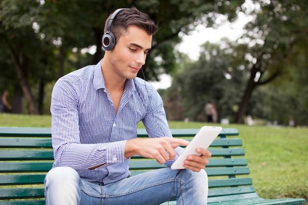 Uomo che ascolta la musica in un parco cittadino