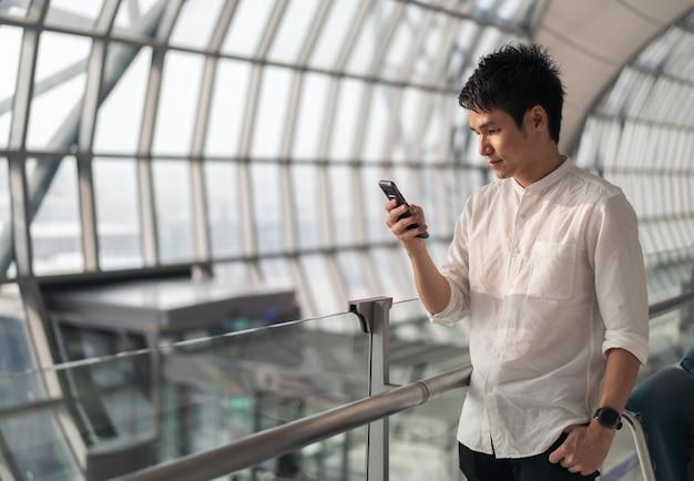 Uomo che aspetta il volo e l'utilizzo di smart phone in aeroporto