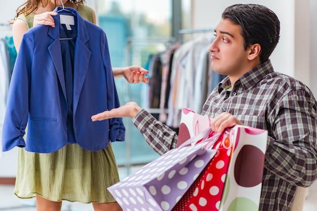 Uomo che aspetta la moglie durante lo shopping natalizio