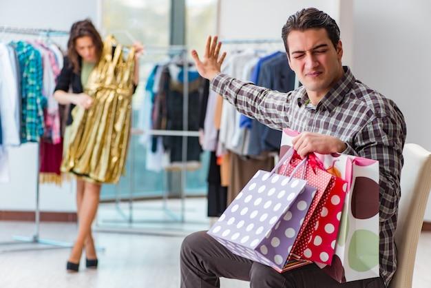 Uomo che aspetta sua moglie durante lo shopping natalizio