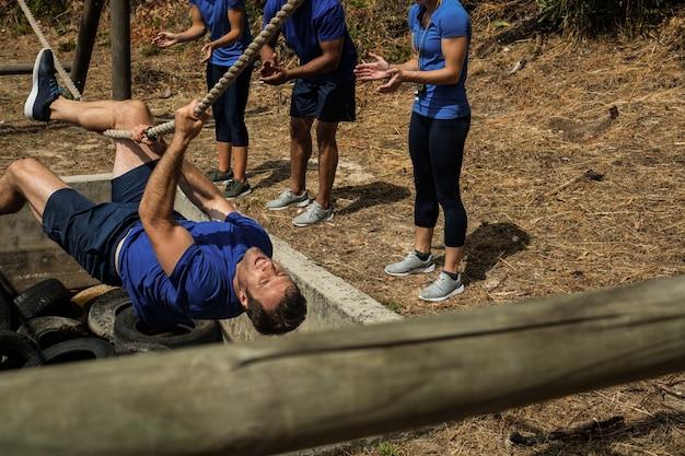Uomo che attraversa la corda durante il percorso ad ostacoli mentre la gente lo applaude