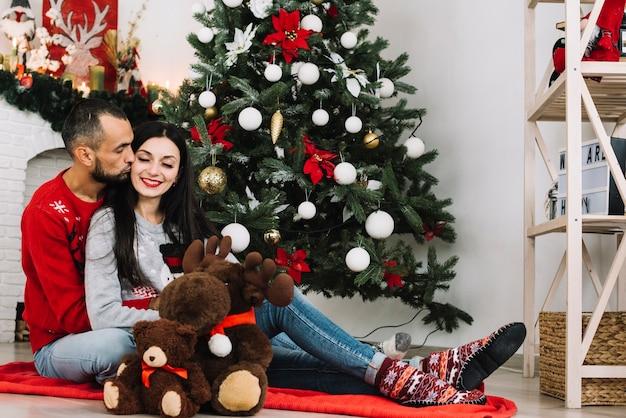 Uomo che bacia la donna vicino a giocattoli morbidi