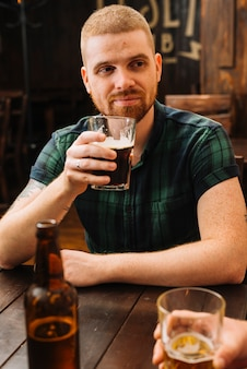 Uomo che beve birra al bar