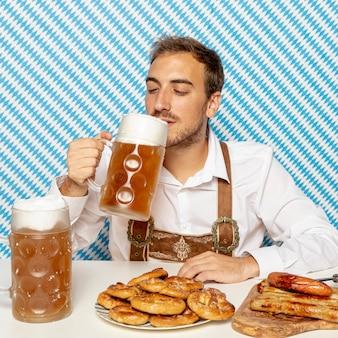 Uomo che beve birra con cibo tedesco