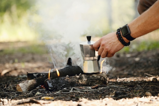 Uomo che beve caffè nella foresta