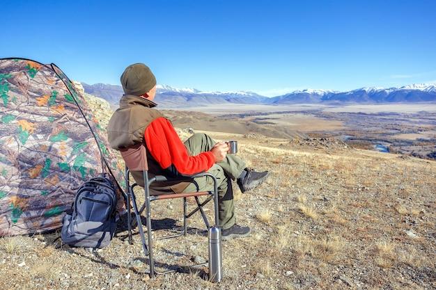 Uomo che beve tè o caffè in montagna. concetto di campeggio di viaggio, trekking ed escursionismo.