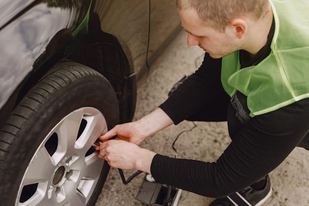 Uomo che cambia ruota dopo un guasto alla macchina