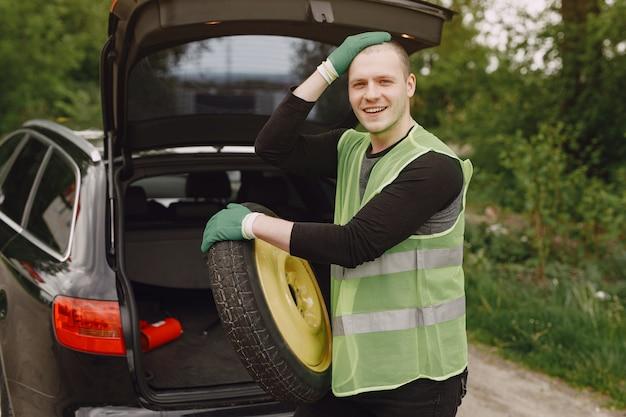 Uomo che cambia ruota rotta sull'automobile
