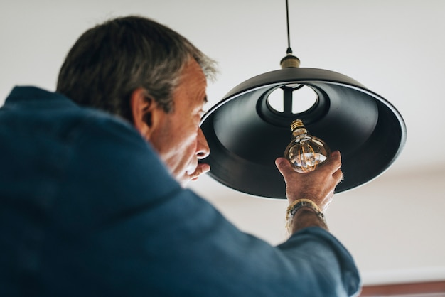 Uomo che cambia una lampadina nella sua casa
