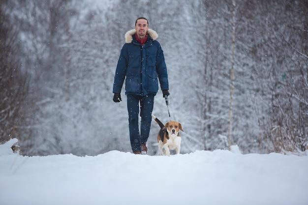 Uomo che cammina con il cane da lepre del cane in inverno. giorno nevica