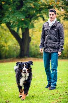 Uomo che cammina il suo cane nel parco di caduta