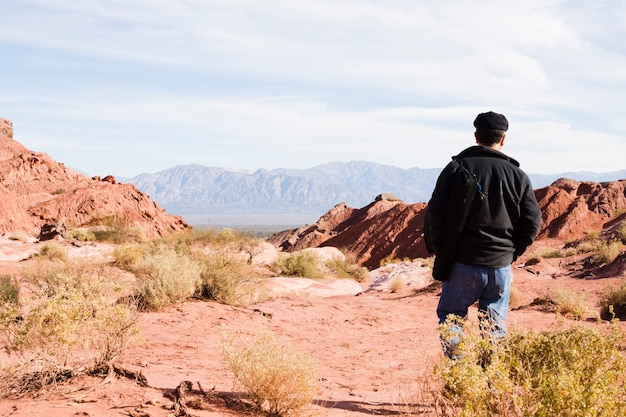 Uomo che cammina nel paesaggio desertico