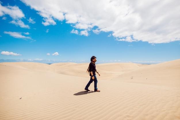 Uomo che cammina su un paesaggio di dune del deserto. uomo che fa un giro turistico tra le dune in una calda giornata estiva.