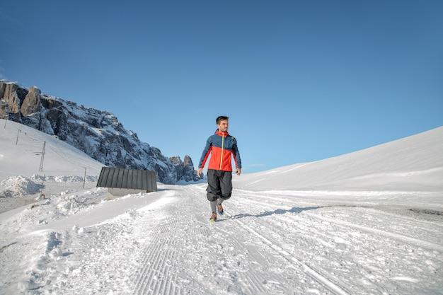 Uomo che cammina su una strada in alta montagna