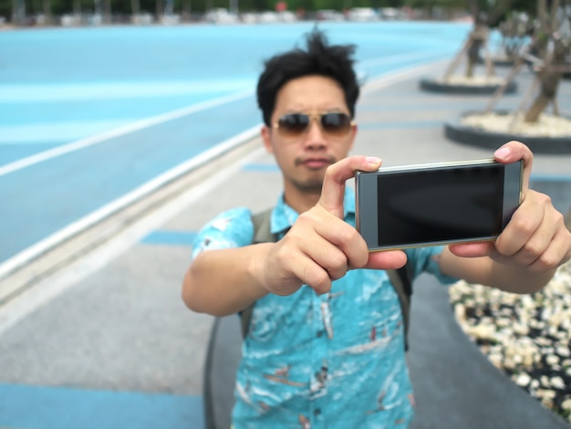 Uomo che cattura foto o selfie con il telefono