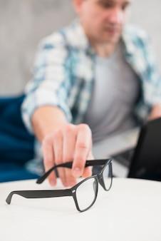 Uomo che cattura gli occhiali alla moda dal tavolo