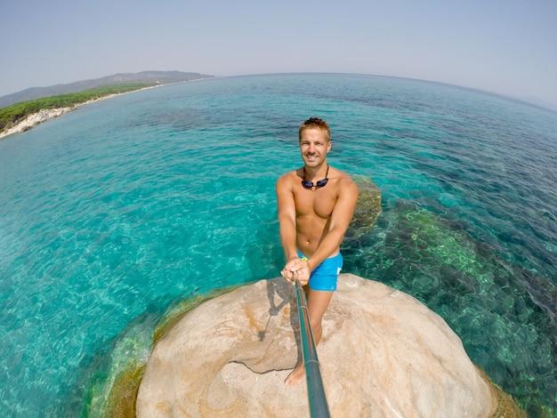 Uomo che cattura selfie azione rock mare vacanze estive.