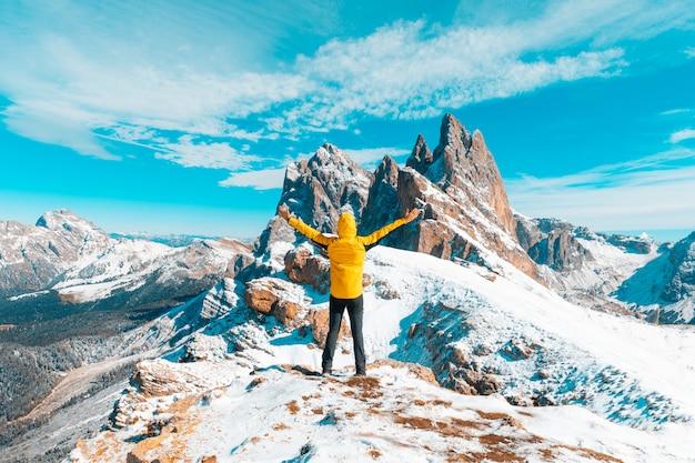 Uomo che celebra il successo in cima alla montagna innevata