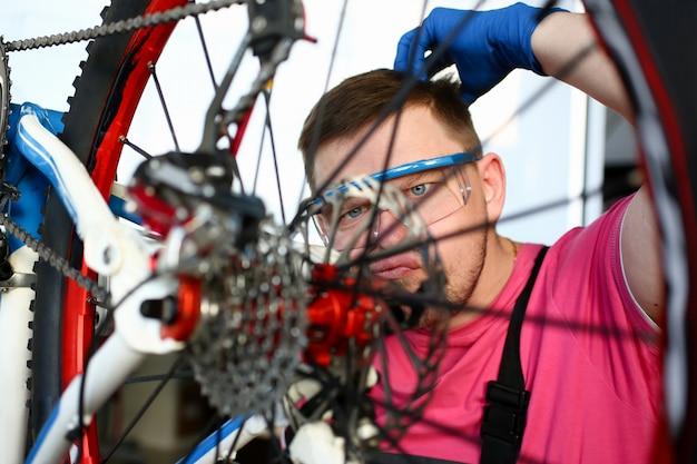 Uomo che cerca di affrontare il meccanismo rotto della bicicletta.