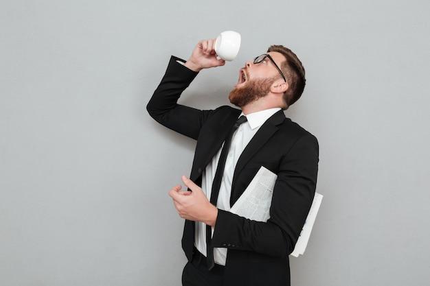 Uomo che cerca di bere l'ultima goccia di caffè da una tazza