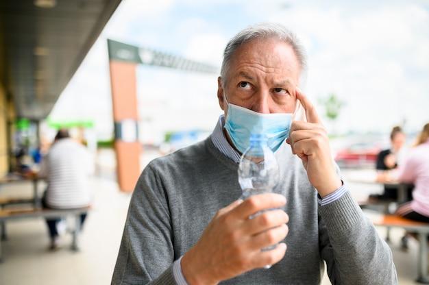 Uomo che cerca di bere una bottiglia di acqua che indossa una maschera