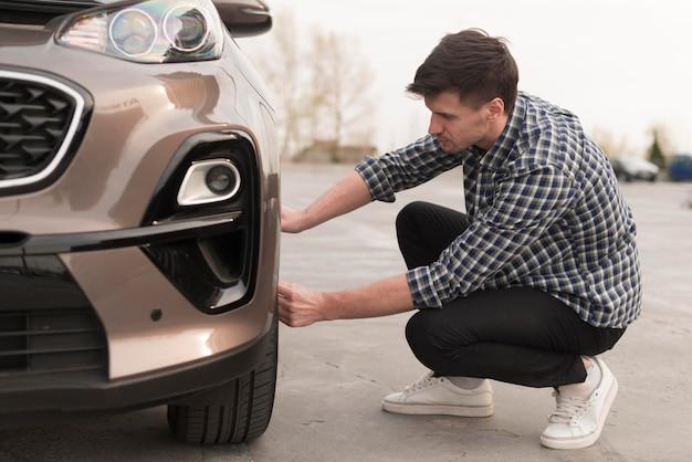 Uomo che cerca di sostituire la ruota dell'auto