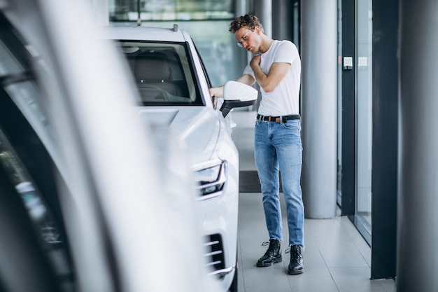 Uomo che cerca un'auto in uno showroom di auto