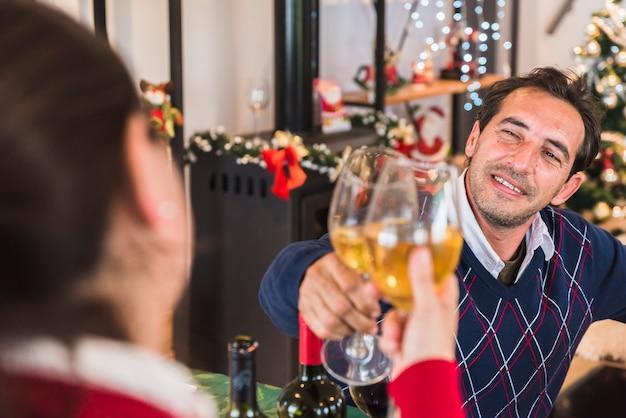 Uomo che clanging bicchiere di vino con donna