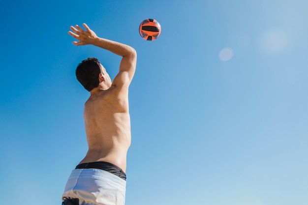 Uomo che colpisce pallavolo in una giornata di sole