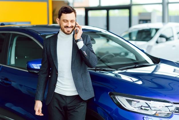 Uomo che compra l'auto. uomo d'affari in un salone di automobile