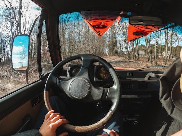 Uomo che conduce l'automobile del suv dalla strada forestale