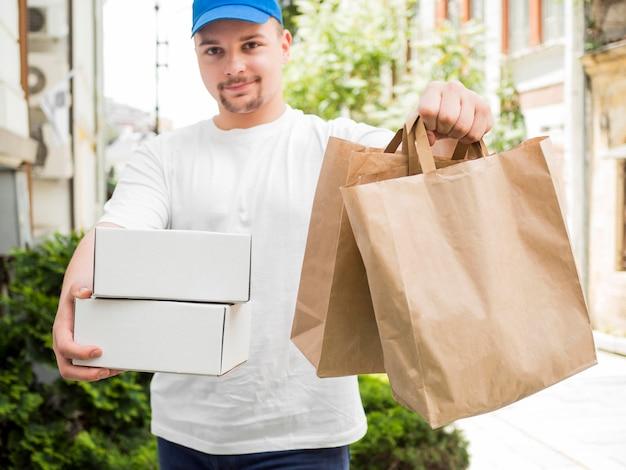 Uomo che consegna sacchetti e scatole vista frontale