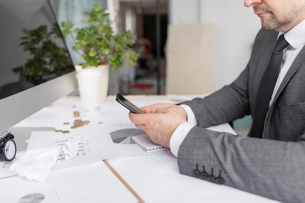 Uomo che controlla il suo telefono al lavoro